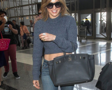 05/26/2015 - Jennifer Lopez - Jennifer Lopez Sighted Arriving at LAX Airport on May 26, 2015 - Los Angeles International Airport - Los Angeles, CA, USA - Keywords: 3/4 Length Shot, Black Pocketbook, Purse, Handbag, Bag, Blue Bell Bottom Jeans, Blue Denim Jeans, Blue Pants, Belly, Blue Sweater, Blue Half Length Sweater, Sunglasses, Shoulder Length Wavy Brown Hair, Brunette, Ring, Rings, Bracelet, Vertical, American actress, author, fashion designer, dancer, producer, singer, California, Arts Culture and Entertainment, Celebrities, Celebrity, Candid Orientation: Portrait Face Count: 1 - False - Photo Credit: STPR / PRPhotos.com - Contact (1-866-551-7827) - Portrait Face Count: 1