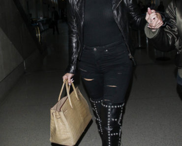 "01/15/2016 - Khloe Kardashian - Khloe Kardashian Sighted Arriving at LAX Airport on January 15, 2016 - Los Angeles International Airport - Los Angeles, CA, USA - Keywords: Thigh High Black Boots with studs, Full Length Shot, Gold Pocketbook, Purse, Handbag, Bag, Vertical, torn black pants, Sportswear, black denim pants, black leather jacket, black jacket, Shoulder Length wavy blond hair, sunglasses, ""Keeping Up with the Kardashians"", ""Dash Dolls"", Reality Television Star, Reality TV, Woman, California, Arts Culture and Entertainment, Celebrities, Celebrity Sightings, Person, People, Candid, Walking, Travel Orientation: Portrait Face Count: 1 - False - Photo Credit: STPR / PRPhotos.com - Contact (1-866-551-7827) - Portrait Face Count: 1"